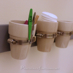 Bathroom storage with mini flower pots, wood, and pipe clamps