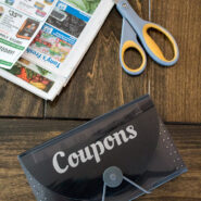 """small expandable file folder with the word """"coupons"""" on it on a table with newspaper coupons and scissors"""