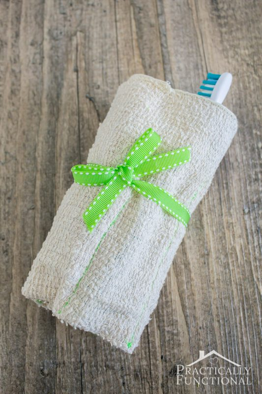 diy roll up toiletry bag made from a washcloth—rolled up and tied with a green ribbon