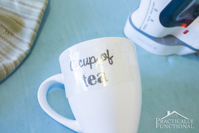 white ceramic mug being personalized with heat transfer vinyl and a household iron in the background
