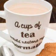 closeup of heat transfer vinyl design on ceramic mug on top of plate with cookies and a spoon