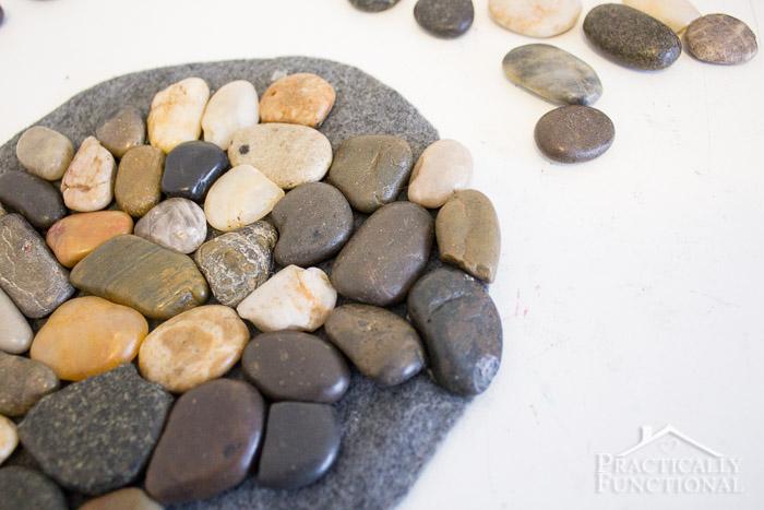 river rocks glued onto a piece of felt and slightly overhanging the edge to make a river rock trivet