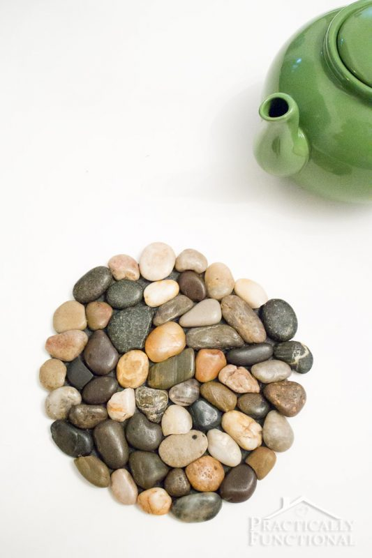 diy river rock trivet and spout of green tea kettle on white background