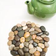 diy river rock trivet and green tea kettle on white background