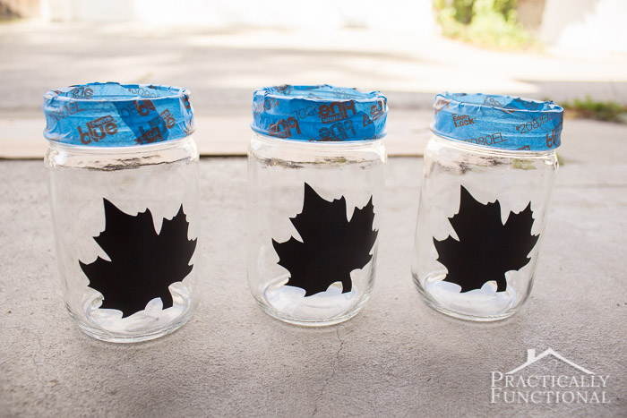 mason jars with adhesive vinyl stickers on them and painter's tape around threads to make silhouette jars