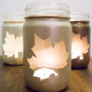mason jar candle holders spray painted in gold with leaf-shaped unpainted area to see candle through