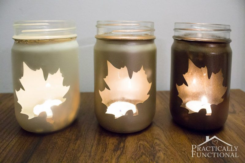 three mason jar silhouette luminaries with tea light candles inside that show through a leaf-shaped silhouette hole in the paint