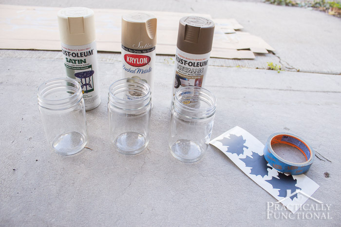 supplies for making silhouette jars—mason jars, spray paint, adhesive vinyl stencils, and painters tape
