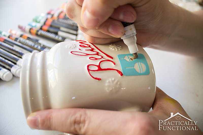 hands using painters opaque paint pens and adhesive stencils on a white ceramic mug