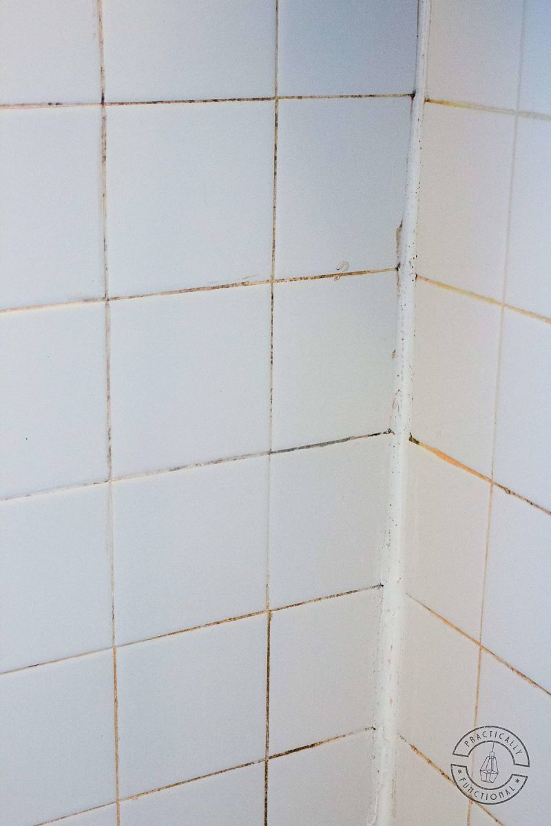 white tile wall with dirty black grout lines and orange hard water stains