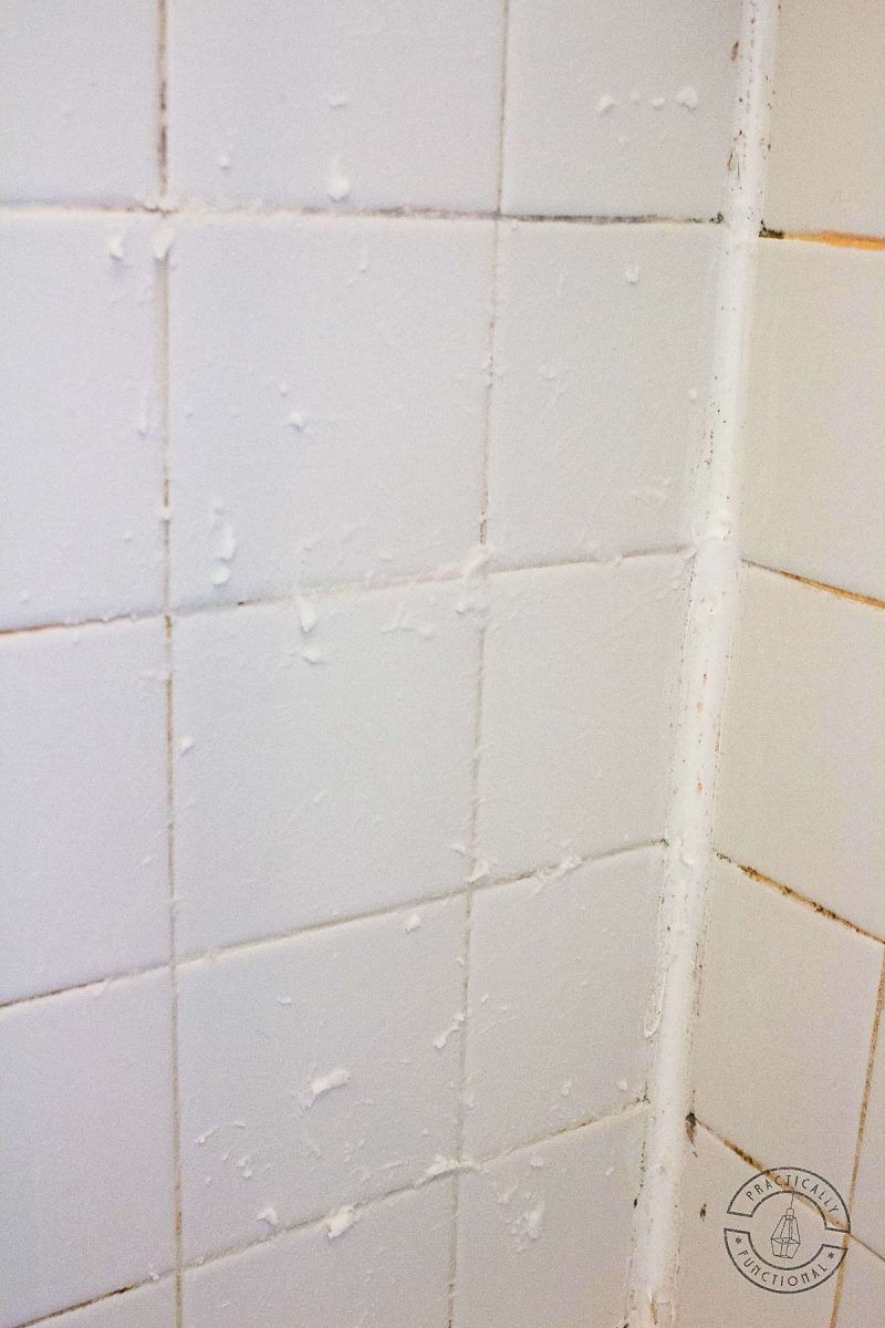white tile wall with baking soda and bleach grout cleaner paste covering dirty black grout and orange hard water stains