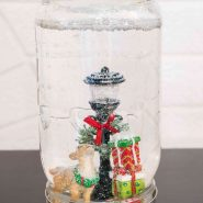 homemade snow globe in a mason jar with reindeer, light post, and presents miniature figurines