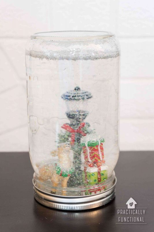 homemade snow globe in a mason jar with glitter floating in glycerine to look like snow