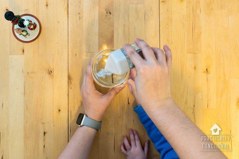 shake glitter into mason jar to make homemade snow globe