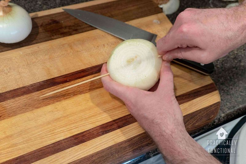 Skewer onions before cutting them into slices