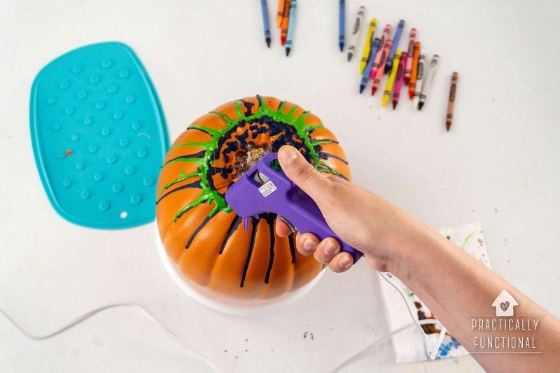 Melt additional crayons onto pumpkin using hot glue gun