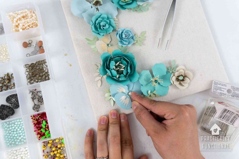 Use straight pins or glue to add beads buttons or baubles to decorate diy paper flowers