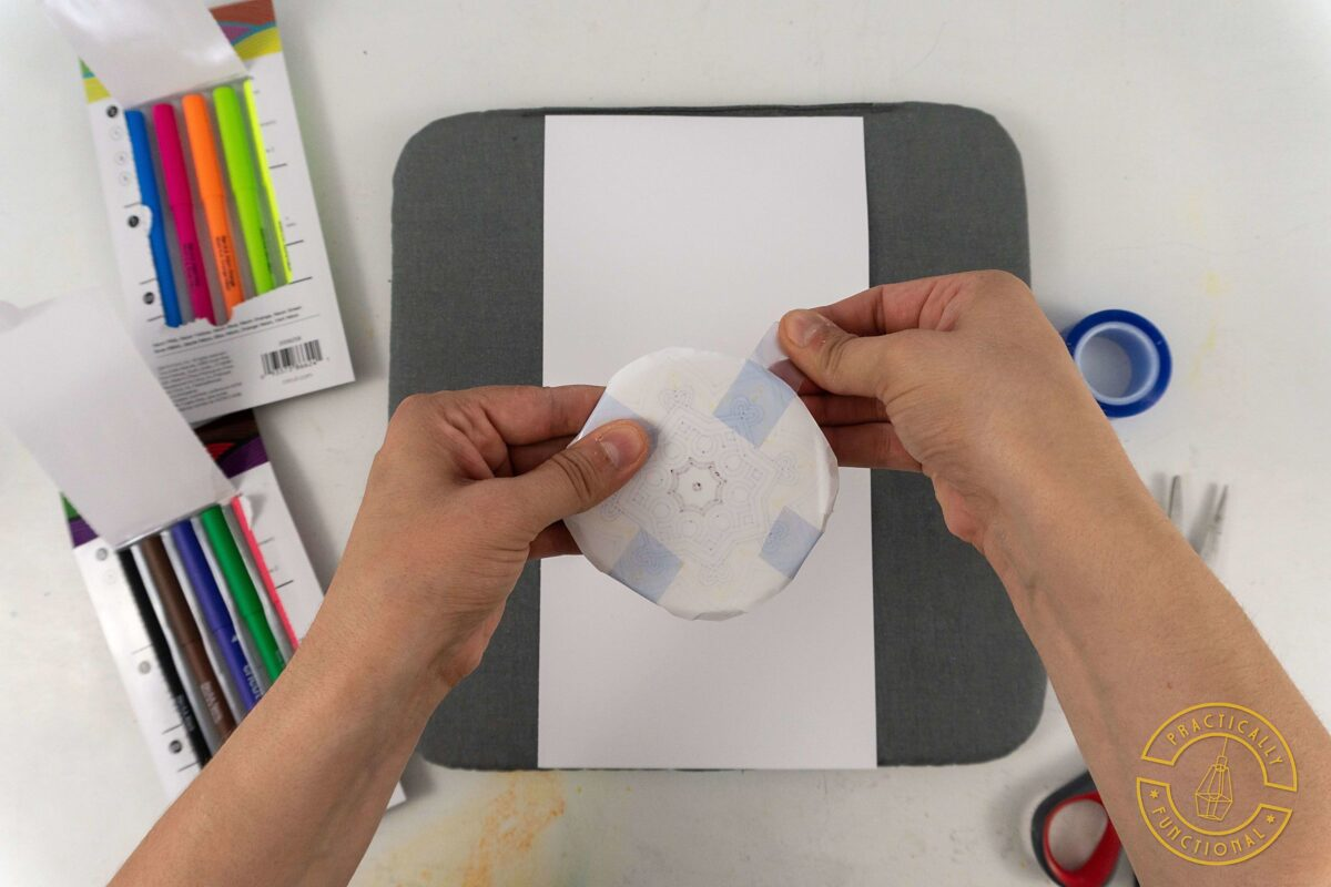 Use heat resistant tape to attach your design drawn with cricut infusible ink pens and markers to a ceramic coaster