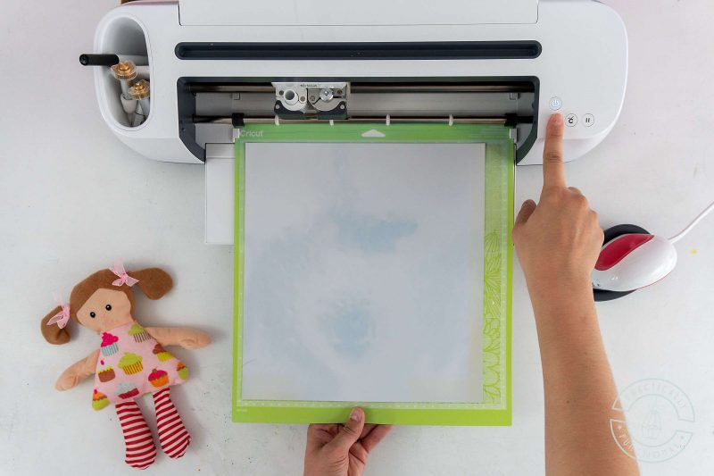 Load heat transfer vinyl into the cricut for cutting before pressing onto stuffed doll with cricut easypress mini