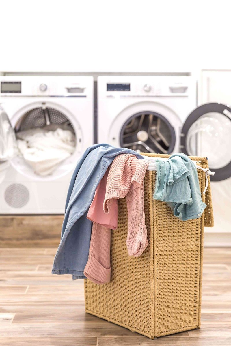 wicker laundry hamper full of clothes in front of a white washing machine and white dryer