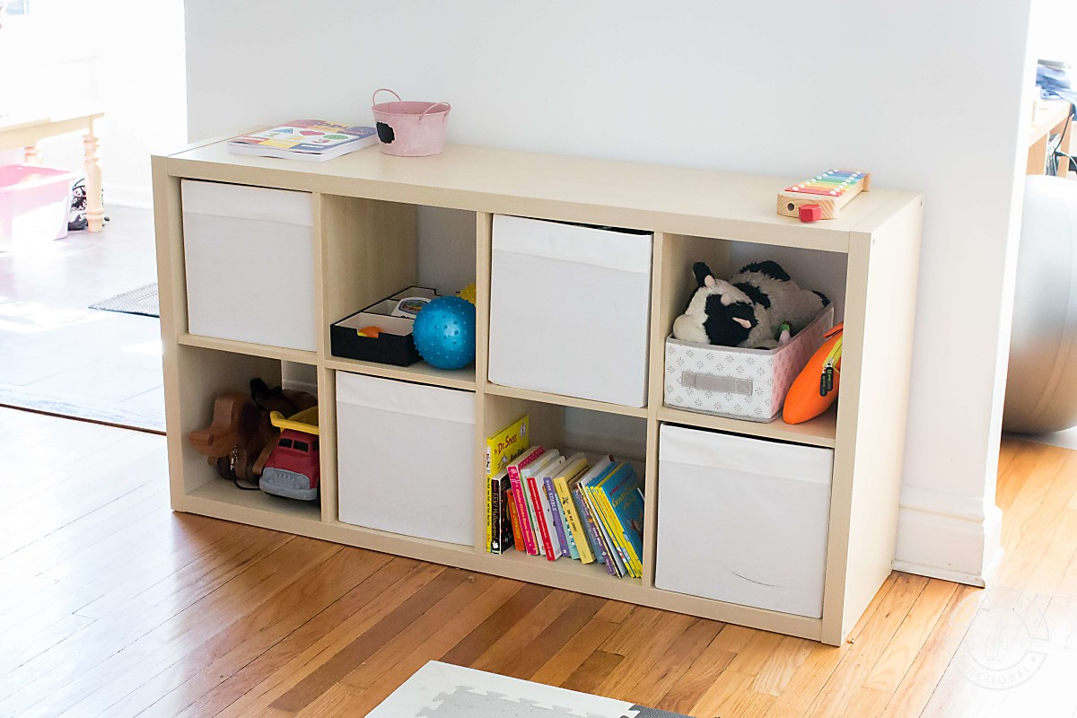 ikea kallax birch colored 4x2 cubby storage unit with white ikea drona fabric bins used as toy storage in a playroom