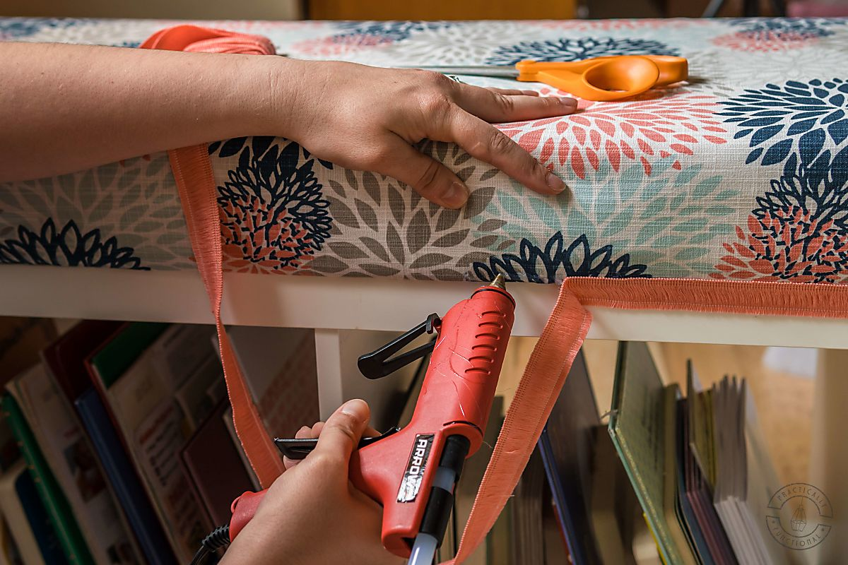 woman attaching pink fringe trim to diy bench cushion using a hot glue gun