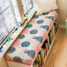 diy bench seat cushion on top of ikea kallax cubby storage unit being used as a window seat and book storage