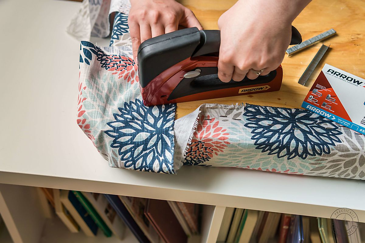 woman stapling upholstery fabric around corner of diy bench cushion using arrow t50 red stapler