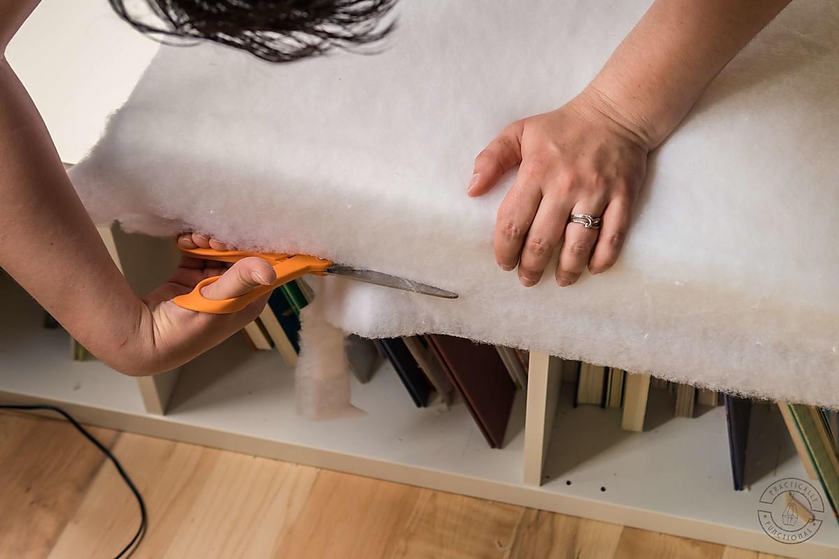 woman using scissors to trim batting flush to bottom of diy bench cushion