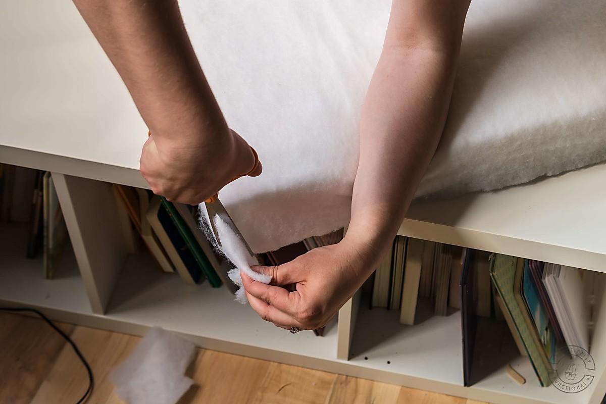 woman using scissors to trim batting at corner of diy bench cushion